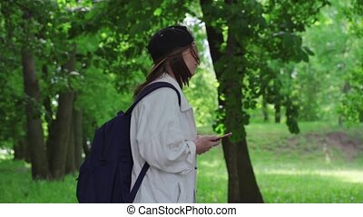 Side view of a beautiful woman in cap walking in the park ...