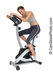 Side view of a beautiful young woman on stationary bike