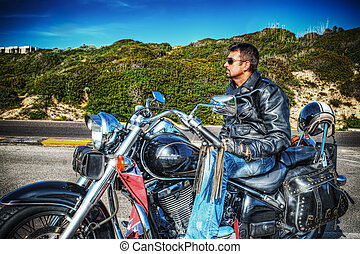side view of a biker on a classic motorcycle