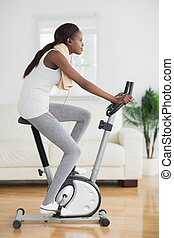 Side view of a black woman doing exercise bike