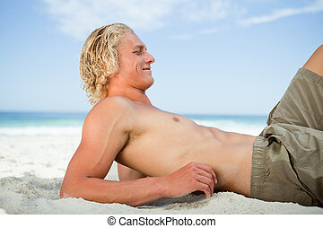 Side view of a blonde man lying on the beach