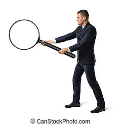 Side view of a businessman holding big magnifier with both hands isolated on white background