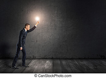 Side view of a businessman with glowing light bulb in outstretched arm going through darkness