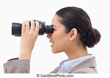Side view of a businesswoman looking through binoculars ...