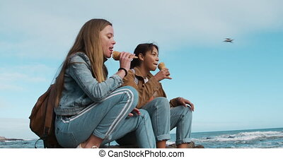 Side view of a Caucasian and a mixed race girl eating ice ...