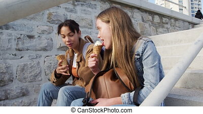 Side view of a Caucasian and a mixed race girl enjoying time hanging out together on a sunny day, eating ice cream, sitting on the stairs in a promenade by the sea,  in slow motion.