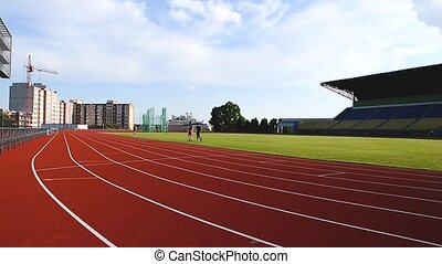 Side view of a Caucasian athletes practicing at a sports stadium, running on racing track, Track and Field Sports Training in Stadium