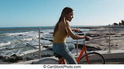 Side view of a Caucasian girl riding a bike seaside - Side ...