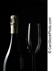 Side view of a champagne bottle and glass on a black background.