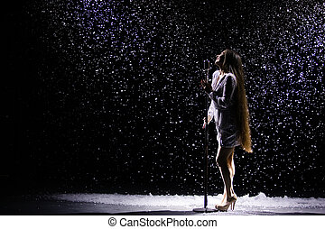 Side view of a charming young woman in an evening shiny dress singing into a vintage microphone against the background of falling snow.