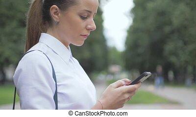 Side view of a college girl text messaging mobile phone in...