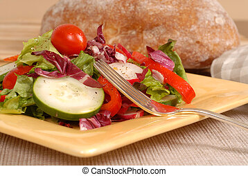 Side view of a crisp healthy salad on a yellow plate with ...