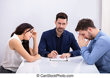 Depressed Couple Sitting In Front Of Judge