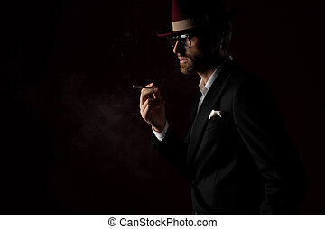 Side view of a dramatic fashion model smoking a cigarette