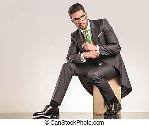 Side view of a elegant business man sitting on a wood box...