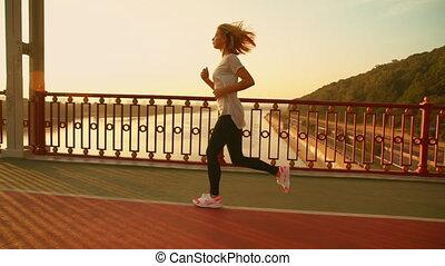 side view of a female runner - girl wearing white t-shirt...