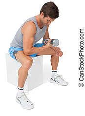 Side view of a fit man exercising with dumbbell