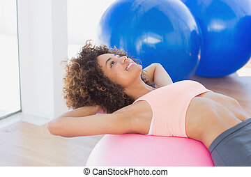 Side view of a fit woman exercising on fitness ball
