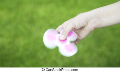 Side view of a girl playing with a spinner in a park - Side...