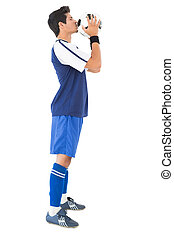 Side view of a handsome football player kissing ball