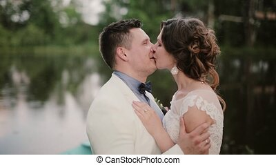 Side view of a happy couple kissing near a pond on their wedding day, happily smiling and enjoying time together