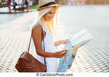 Side view of a happy woman on vacation with map