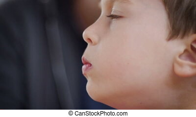 Side view of a little boy puffing up his cheeks while...