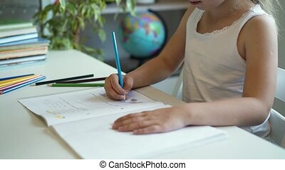 Side view of a little girl doing her homework