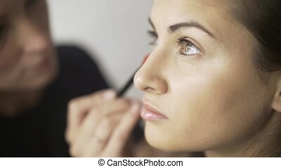Side view of a make up artist applying toning cream to a fair hair girl s face