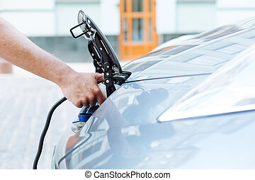 Side view of a male hand charging an electric vehicle