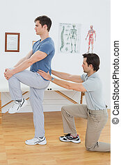 Side view of a male physiotherapist examining mans back