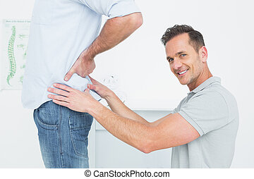 Side view of a male physiotherapist