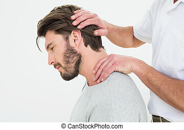 Side view of a man getting the neck adjustment done - Side...