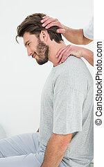 Side view of a man getting the neck adjustment done - Side ...