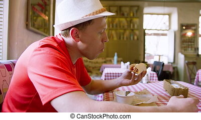 Side view of a man in a hat eating fast food in a cafe, ...
