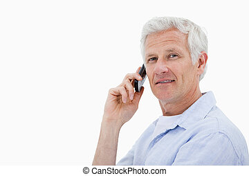 Side view of a man making a phone call while looking at the camera against a white background