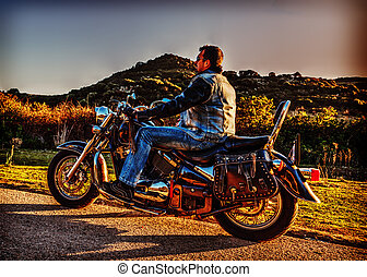 Side view of a man on a classic motorcycle