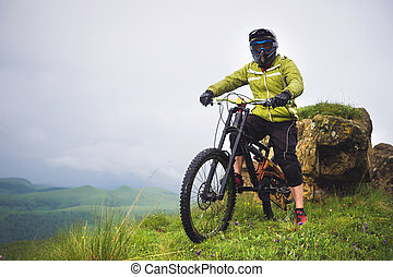 Side view of a man on a mountain bike standing on a rocky terrain and looking at a rock. The concept of a mountain bike and mtb downhill