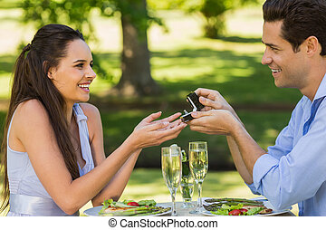 Side view of a man proposing woman while they have a romantic date at an outdoor café