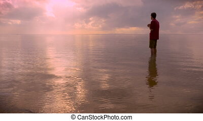 Side view of a man standing in a calm ocean while he bows his head in prayer