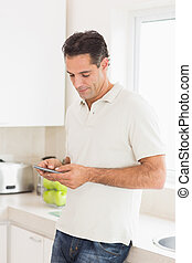 Side view of a man text messaging in kitchen