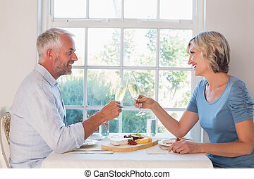 Side view of a mature couple toasting drinks over food