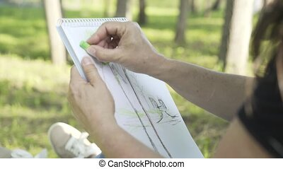 Side view of a middle aged woman sketching in a park