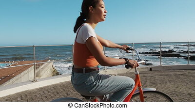 Side view of a mixed race girl riding a bike seaside - Side ...