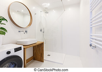 Side view of a modern bathroom interior with a shower, wash basin, round mirror, washing machine and wall radiator