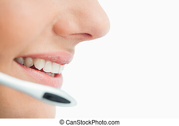 Side view of a mouth speaking in headset against white...