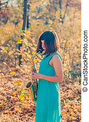 side view of a nice young girl with black hair, dressed in a long blue dress who plays the alto saxophone among yellow leaves in the autumn forest