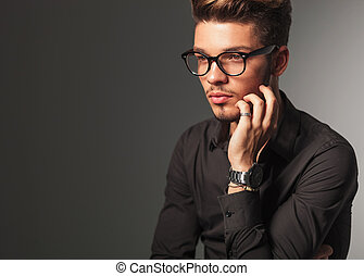 side view of a pensive young man with glasses