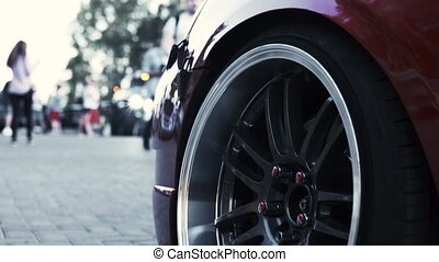 Side view of a red sports car and a stylish wheel