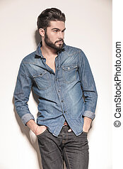 side view of a relaxed young man in jeans clothes looking...